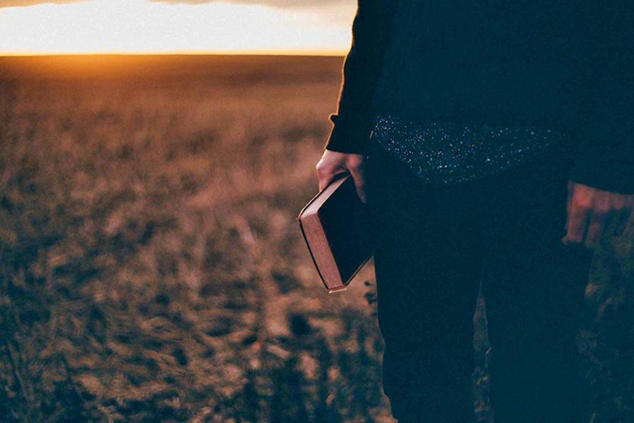 Man standing, holding a bible